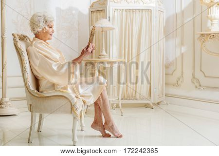 Happy old lady is holding mirror and looking at face with satisfaction. She is sitting on chair and smiling