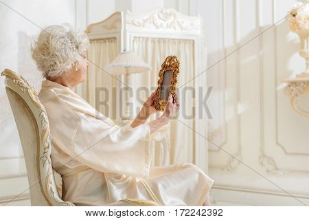 Senior woman is sitting on armchair in her expensive apartment. She is holding frame and looking old photo of her youth with melancholy