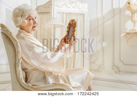 When I was young, I was very beautiful. Mature rich lady is holding frame and looking at camera with sadness. She is sitting on armchair at home