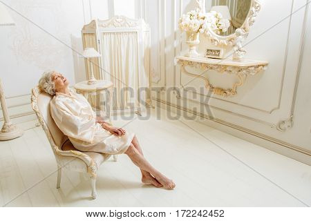 Wealth and luxury. Old woman is sitting on armchair and relaxing. Her eyes are closed with pleasure