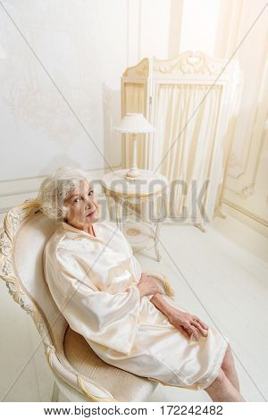 Calm senior lady is resting on chair in her chic apartment. She is looking at camera with serenity
