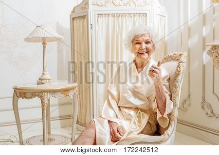 Everything is okay. Happy old woman is sitting on armchair in expensive furnished house. She is giving thumb up and smiling