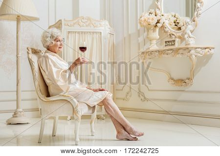 Old woman is drinking wine at home. She is sitting on expensive armchair and looking at glass with melancholy