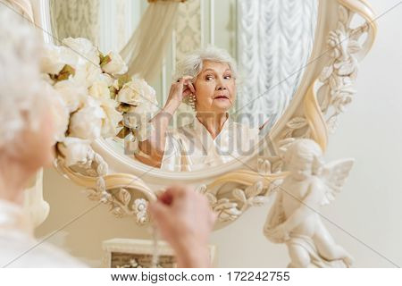 Mature lady is trying on pearl earring at home. She is standing and looking at mirror with interest