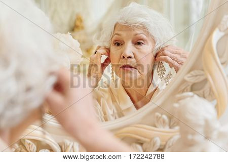 Senior woman is wearing expensive jewelry on her ears. She is looking at mirror pensively