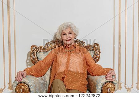 Richness is great. Senior lady is relaxing on comfortable chair and smiling