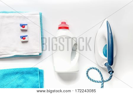 laundry set with bright towels and plastic bottels of detergent on white table background top view