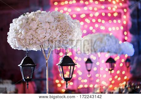 Lights and lanterns in the night. Bokeh Wedding Banquet. The chairs and round table for guests