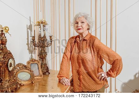 I am proud of my apartment. Serious mature lady is standing with arm akimbo near expensive furniture. She is looking at camera with confidence