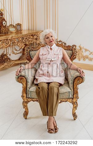 Confident mature queen is sitting on confortable armchair and relaxing