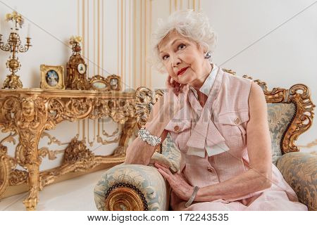 Graceful old lady is relaxing on expensive chair. She is looking forward with pretty smile and posing
