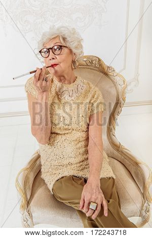 Glamorous senior lady is keeping in mouth tobacco pipe. She is sitting on chair and looking at camera with confidence
