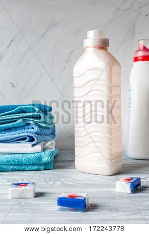 Pile of colorful clean towels with detergent on laundry gray background