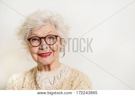Waist up portrait of happy old woman in eyeglasses standing and smiling. Isolated and copy space in right side