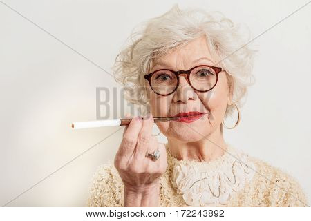 Elegant senior lady is smoking cigarette. She is standing and looking at camera with joy. Isolated on background