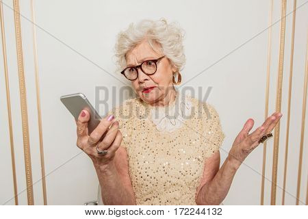 I do not understand in modern technology. Puzzled old lady is holding smartphone and looking at gadget with misunderstanding