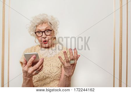 What is that. Shocked senior woman is staring at mobile phone with confusion. She is standing and gesturing with irritation
