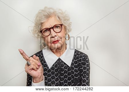 Strict old female teacher is standing and pointing finger up. She is looking at camera with seriousness. Isolated