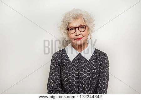 Kind senior lady is standing and looking at camera with joy. She is smiling. Isolated and copy space in left side