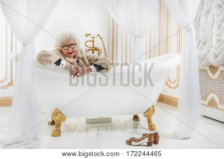 Cheerful old woman is relaxing in bath at home. She is wearing expensive fur coat. Woman is looking at camera and smiling