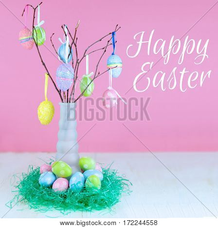 An Easter Tree of sparkly colorful eggs hanging from small tree branches in a tall vase. More eggs around the base in green Easter grass. Wood table with pink background. Text added.