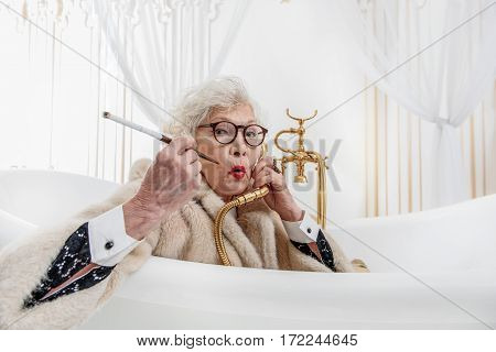 Senior lady is keeping faucet near ear as talking on telephone. She is listening to it with attention. Granny is smoking cigarette while sitting in bath