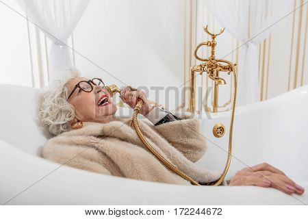 Wealthy but crazy. Old woman is lying in bath and holding tap near ear as phone. She is laughing