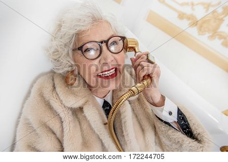 Hello, queen is speaking. Crazy rich mature woman is sitting in bath while wearing fur coat. She is holding faucet near ear as telephone and smiling