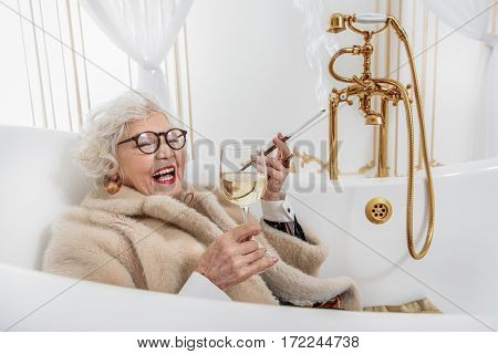 Happy old woman is lying in bath with relaxation. She is drinking wine and smoking cigarette. Woman is laughing while wearing fur coat