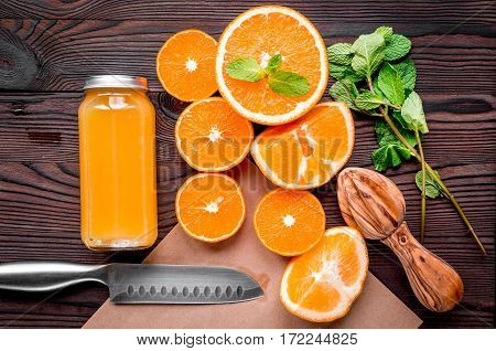 Homemade juice bottles with orange slices and mint leaves on table background top view