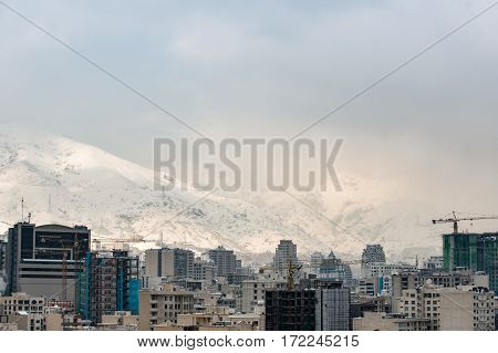 New high buildings among old ones near white snowy mountains