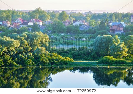 Summer rural landscape with small village in the forest near the river - birds eye view of summer nature. Colorful summer landscape of summer countryside in early summer morning. Summer background