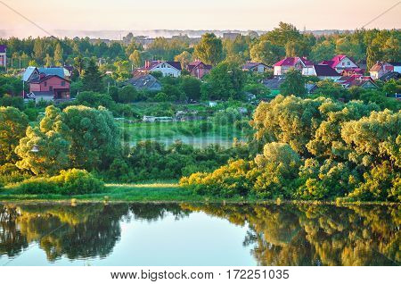 Spring rural landscape with small countryside in the forest near the river in the sunrise. Birds eye view. Spring water landscape in the sunrise. Spring rural landscape view from height. Picturesque spring rural andscape