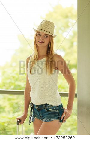 Female fashion trendy summer clothes concept. Attractive young woman wearing sun hat white top and denim shorts fashionable summeral style indoor shot in front of big window