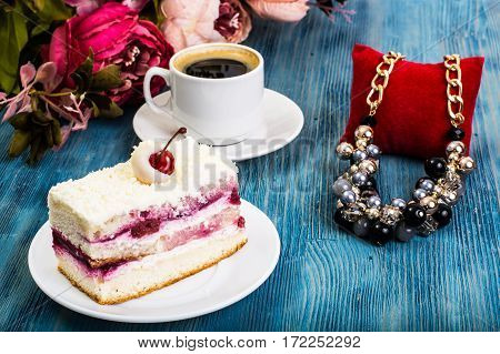 Piece of cake, sponge cakes, cream, cherries, whipped cream on blue background. Studio Photo