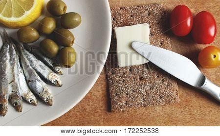 Saltde sprat ith lemon, olives, tomatoes, butter and bread