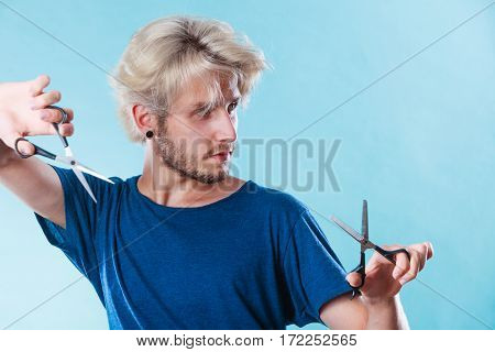 Haircut coiffure haircare concept. Passionate male hairdresser holding scissors showing work tools normal and thinning shears