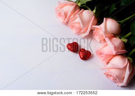 St. Valentine greeting background with five pink rose. Elegant wedding invitation with red glitter hearts. Copy space.