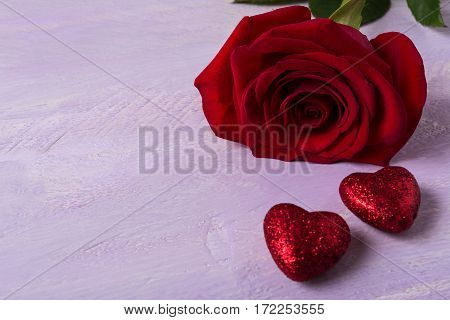 Wedding background with dark red rose and glitter hearts. Elegant St. Valentine greeting card with flower and holiday symbol. Copy space.