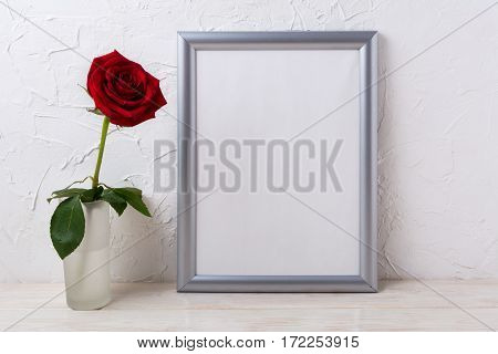Silver frame mockup with red rose in glass vase. Empty frame mock up for presentation design.