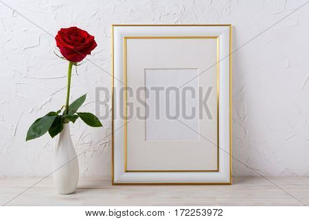 Frame mockup with red rose in elegant vase. Empty gold decorated frame mock up for presentation artwork.