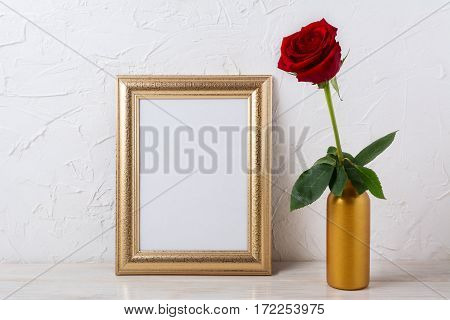 Gold frame mockup with dark red rose in vase. Empty white frame mock up for presentation design.