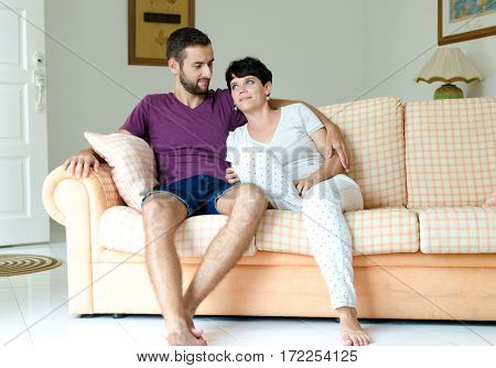 Young couple on the sofa. Man and woman embracing while sitting on the couch.