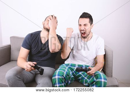 Friends Playing Videogames On Couch.