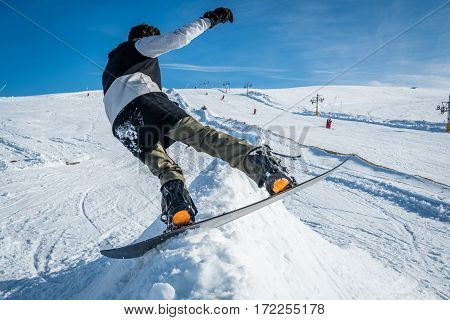 Snowboarder executing a radical slide against blue sky.