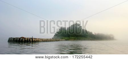 An island with breakwaters in the fog, a river