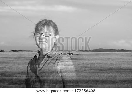 black and white double exposure  image of a caucasian farm woman standing in a field with a tractor sitting in the distance in the summer time.