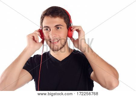 Close up of a young handsome man listening music with red headphones. Isolated white background.