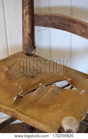 colonial wooden chair with torn leather seat