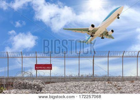 Restricted area fence and Passenger airplane landing beautiful blue sky background